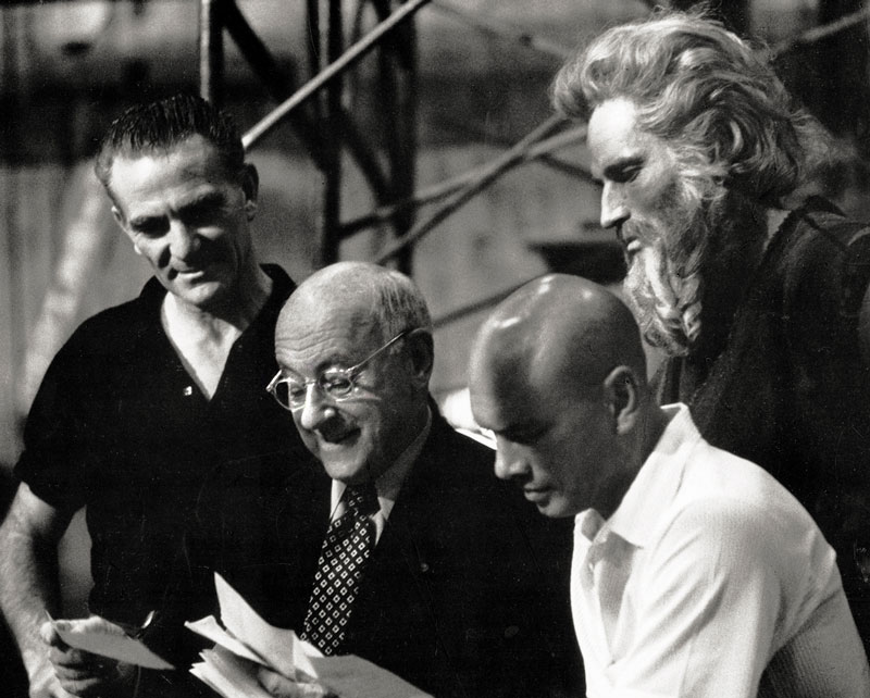 DeMille conferring with associate producer Henry Wilcoxon and stars Yul Brynner, Charlton Heston