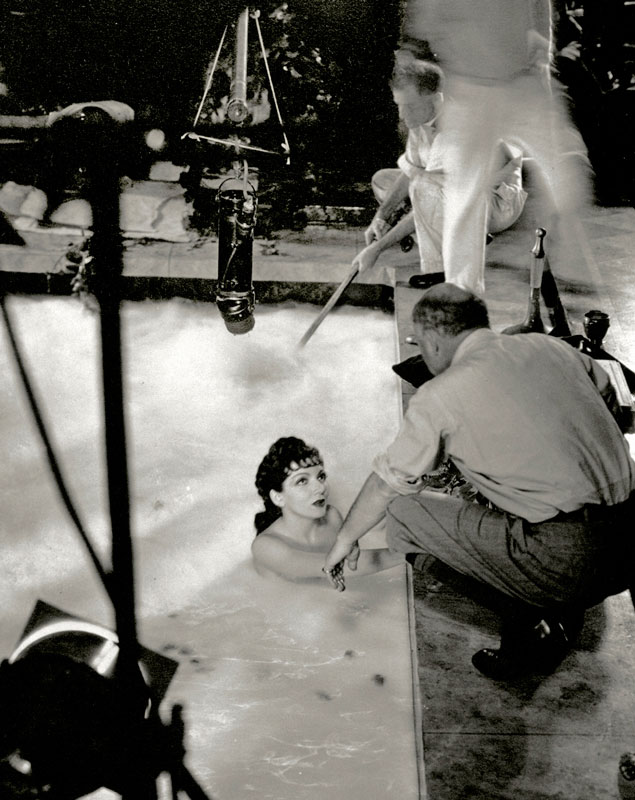 An early microphone hovers over Claudette Colbert and DeMille on the set of The Sign of the Cross (1932)